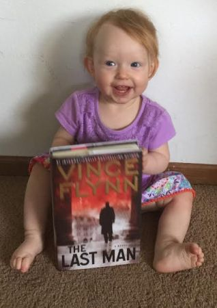 My youngest daughter, Rylee, named after Rapp's wife, with my signed copy of The Last Man, by Vince Flynn